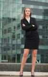 美丽的女实业家常设外部大厦 免版税库存照片