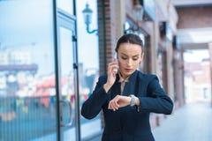 美丽的女实业家检查时间和谈话由智能手机 图库摄影