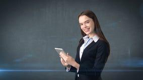 美丽的女实业家调查触摸板并且微笑着,灰色背景 库存照片