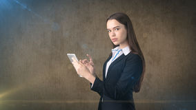 美丽的女实业家调查触摸板,棕色背景 免版税库存图片
