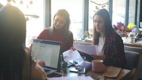 美丽的女实业家谈论文件在一杯咖啡的一个咖啡馆 股票录像