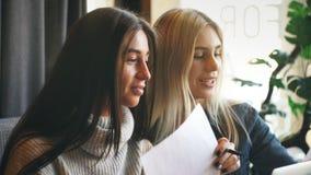 美丽的女实业家谈论文件在一杯咖啡的一个咖啡馆 影视素材