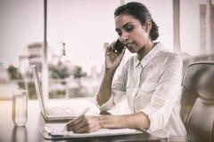 美丽的女实业家运作的坐在她的书桌 免版税库存图片