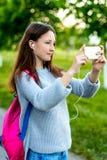 美丽的女小学生女孩少年 夏天本质上 在他的手上拿着在他的背包后的一个智能手机 照片 免版税库存图片