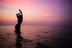 美丽的女性剪影在晚上海 库存照片