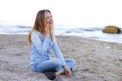 美丽的女性发表演讲关于机动性与微笑并且坐海滩n 免版税库存照片