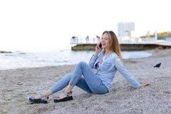 美丽的女性发表演讲关于机动性与微笑并且坐海滩n 库存图片