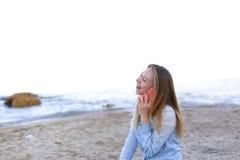 美丽的女性发表演讲关于机动性与微笑并且坐海滩n 免版税图库摄影