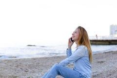 美丽的女性发表演讲关于机动性与微笑并且坐海滩n 免版税库存图片