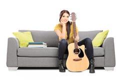 美丽的女性吉他弹奏者坐沙发 免版税库存图片