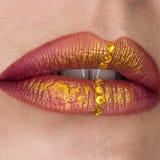 美丽的女性嘴唇特写镜头 红色口红,金油漆 在嘴唇的首饰 免版税库存图片