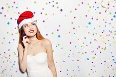美丽的女性式样穿戴圣诞老人帽子画象  白色礼服和红色嘴唇 五彩纸屑的体贴的女孩 逗人喜爱的设计 免版税库存图片