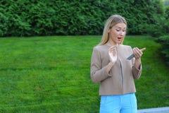 美丽的女性拿着手机,看屏幕并且表达 免版税图库摄影