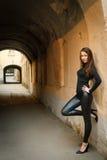 美丽的女性模型最近的常设墙壁年轻&# 库存照片