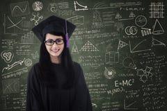 美丽的女性毕业生微笑在类 免版税图库摄影