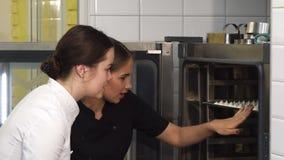 美丽的女性糖果商和她的助理审查的merengues在烤箱 影视素材