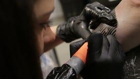 美丽的女性纹身花刺艺术家在她的客户做纹身花刺和谈话与他 股票视频
