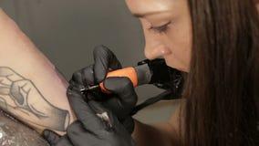 美丽的女性纹身花刺艺术家在手边做纹身花刺客户,照相机移动 股票视频
