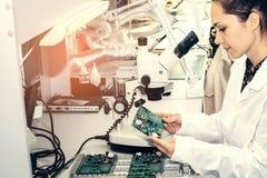 美丽的女性计算机专家专业技术员审查的单板计算机在一个实验室在工厂 免版税库存照片