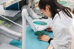 美丽的女性计算机专家专业技术员审查的单板计算机在一个实验室在工厂 免版税图库摄影