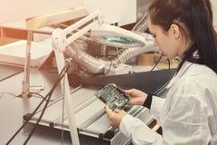 美丽的女性计算机专家专业技术员审查的单板计算机在一个实验室在工厂 库存照片