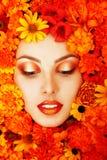 美丽的女性面孔秀丽画象与橙色花的 免版税库存图片