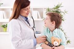 美丽的女性医生审查的微笑的孩子 免版税库存图片