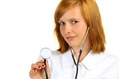 美丽的女性医生(在听诊器的焦点) 免版税库存照片
