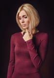 美丽的女性画象看照相机的红色衣物的 免版税库存图片