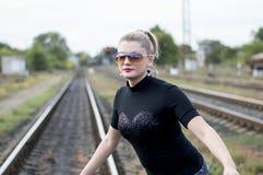 美丽的女服在路轨的太阳镜 免版税库存照片