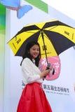 美丽的女主人陈主持开幕式 在雨举行伞 免版税库存图片