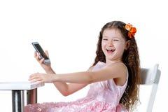 美丽的女婴谈话在白色背景隔绝的礼服的电话 免版税库存照片