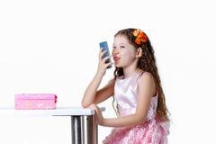 美丽的女婴谈话在白色背景隔绝的礼服的电话 库存图片