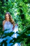 美丽的妇女、新娘有蓝眼睛的和棕色头发通过叶茂盛森林,森林地走在一明亮的晴朗的夏天` s天 免版税库存照片