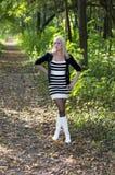 美丽的妇女一条森林小径的金发碧眼的女人在秋天 库存照片