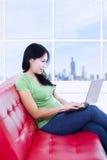 美丽的妇女与在红色沙发的膝上型计算机一起使用 库存照片