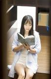 年轻美丽的妇女中国画象在书店读书 免版税库存图片