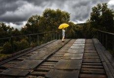 美丽的妇女举行黄色伞和走在一座老桥梁在乡下在雨下 免版税库存照片