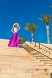 美丽的妇女佩带的帽子和桃红色裙子 免版税库存图片