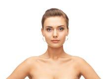美丽的妇女佩带的金耳环 免版税库存照片