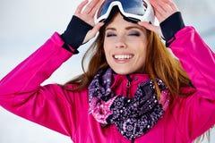 美丽的妇女佩带的风镜在多雪的冬天 免版税库存图片