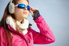 美丽的妇女佩带的风镜在多雪的冬天 免版税库存照片