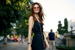 年轻美丽的妇女佩带的玻璃和戴在街道的一个帽子在晚上 库存照片