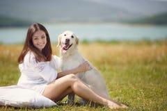 美丽的妇女使用与在草甸的狗 库存照片