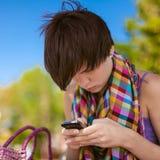 年轻美丽的妇女写SMS 免版税库存图片