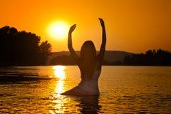 年轻美丽的妇女剪影在日落天空的河 在海滩的女性完善的身体等高在暮色风景 免版税库存照片