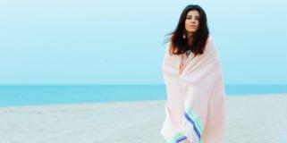 美丽的妇女包裹了自己与在海滩的毯子 库存照片