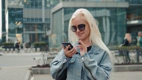 美丽的妇女发一个正文消息使用在她的智能手机的app,当走在街道模型金发碧眼的女人时 影视素材