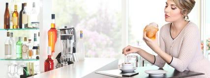 美丽的妇女吃早餐在一个咖啡馆,用新月形面包和c 免版税库存图片