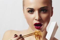 美丽的妇女吃着noodles.red嘴唇。中国棍子。快餐 免版税库存照片